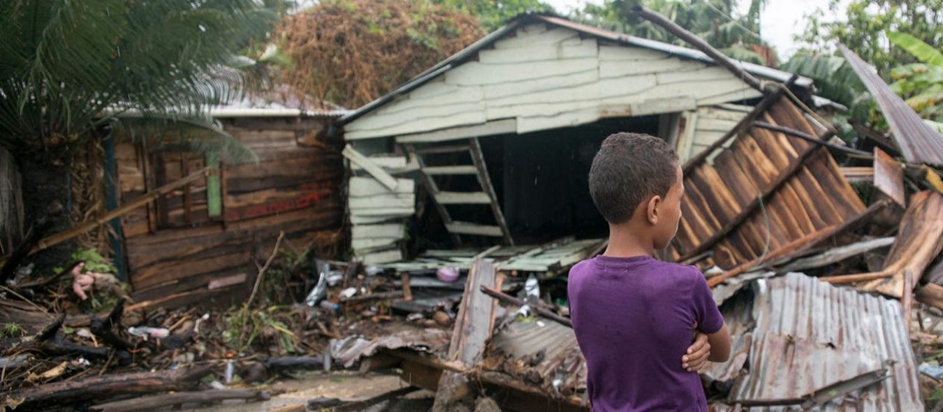 boy standing at collapsed home after hurricane irma hit