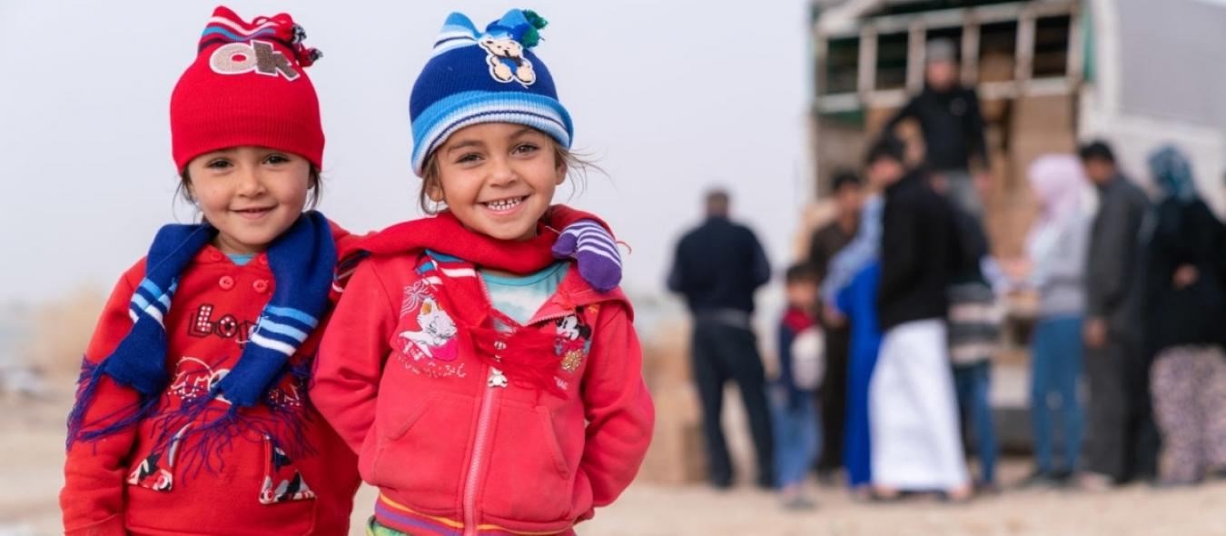 2 enfants syriens sourient à la caméra après avoir reçu des kits de vêtements d'hiver de l'UNICEF et de son partenaire Mateen.