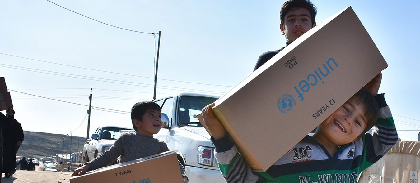 Chlildren with UNICEF aid boxes.