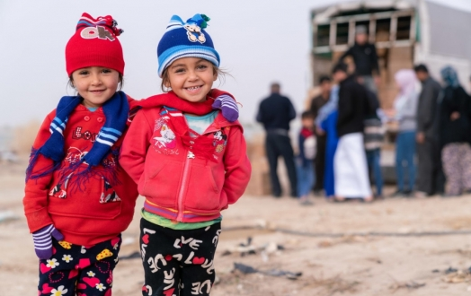 2 Syrian children smile at camera after receiving winter clothing kits from UNICEF and its partner Mateen.