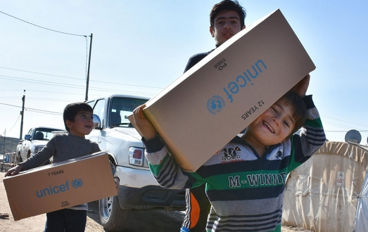 Boys holding UNICEF aid boxes.