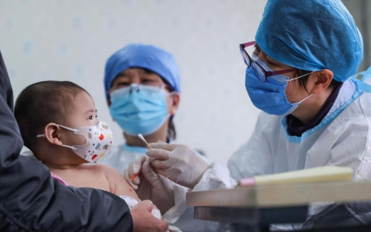 A baby receives a vaccine shot at a community health centre