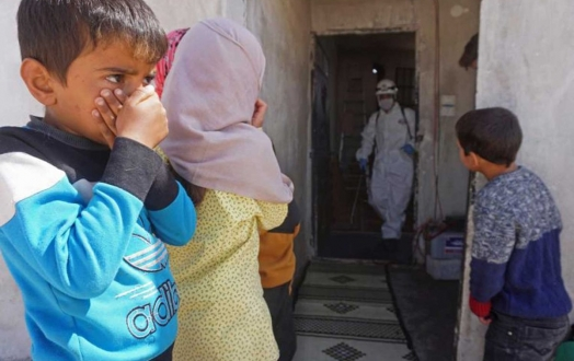 Syrian children watch as a school is disinfected, to prevent the spread of the coronavirus