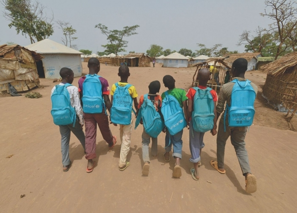 Group of boys carry UNICEF backpacks and walk towards thatch huts and tent shelters in an area of the Gado site for refugees from the Central African Republic.