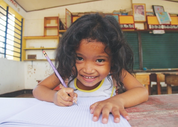 5-year-old girl sits with notebook and pencil inside a school building partly damaged by the typhoon Haiyan in coastal village of Cogon, Palo, Leyte.