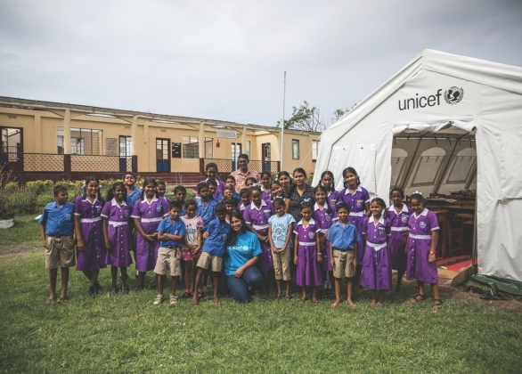 Students and their teachers stand in front of a UNICEF-provided school tent.