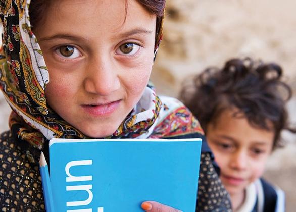 Un enfant avec des fournitures scolaires indispensables : un crayon et un cahier d'exercices