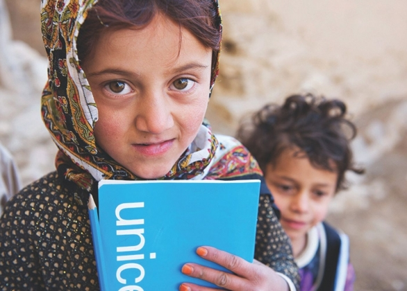 A girl holds school essentials: a pencil and textbook.
