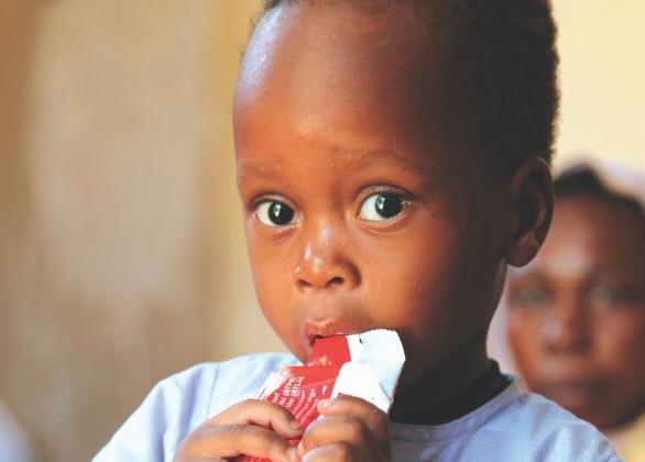 Un garçon qui mange un sachet de Plumpy'Nut (MD)