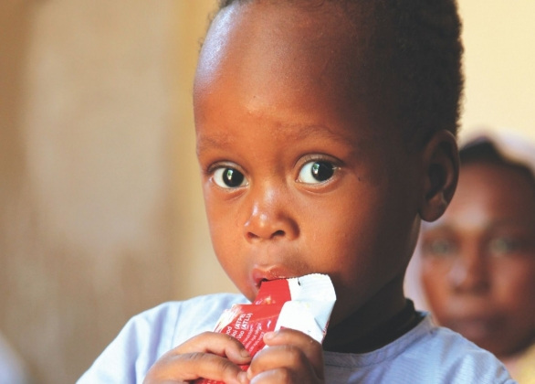 A boy eats a package of Plumpy'Nut® at the UNICEF-assisted ALIMA Therapeutic Centre for malnourished children.
