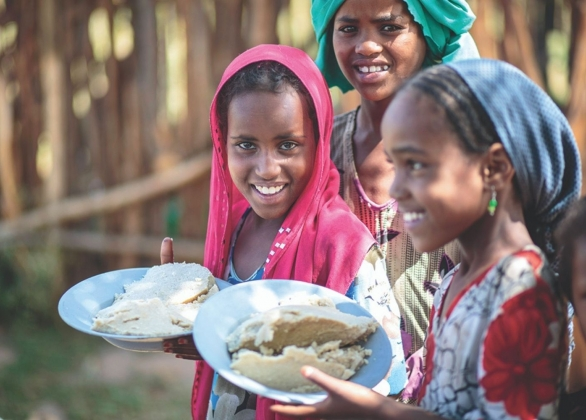 smiling girls hold plates of food
