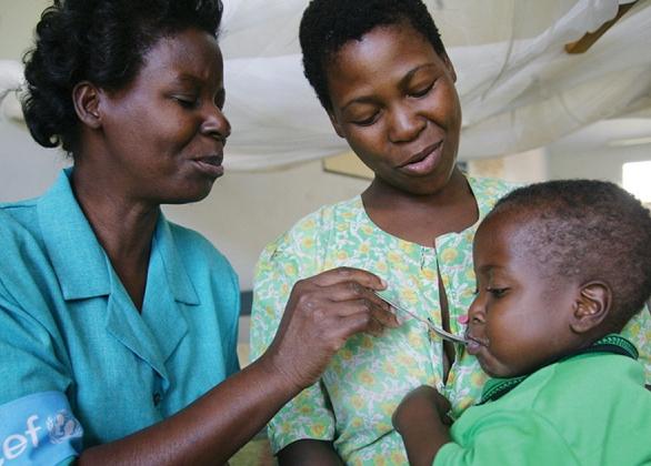 Deux femmes nourrissent un bébé.