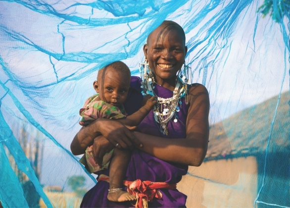 A smiling mother holds her child, standing inside a bed net that protects them from mosquitoes.