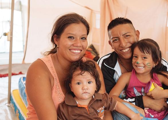 Famille souriante dans un abri temporaire