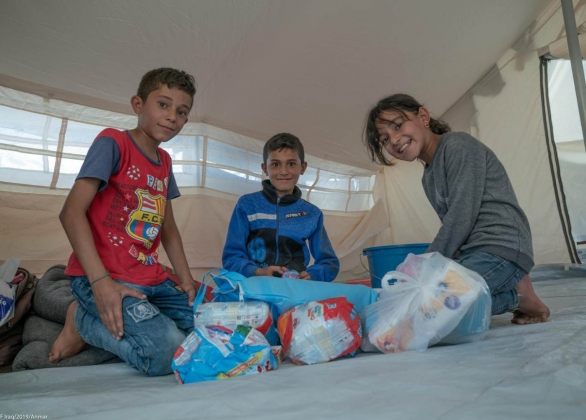 Three children open the Baby and Family Hygiene Kits provided by UNICEF inside their tent at the Barderash camp.
