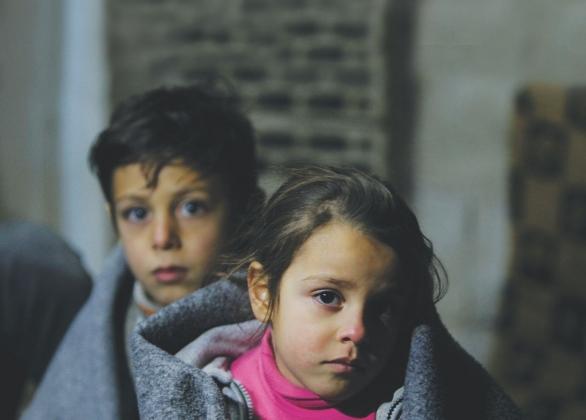 Deux enfants enveloppés dans des couvertures d'urgence