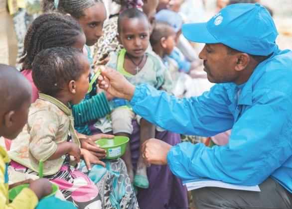 A health specialist at UNICEF Ethiopia Tigray office feeds Bertukan a nutritious porridge.