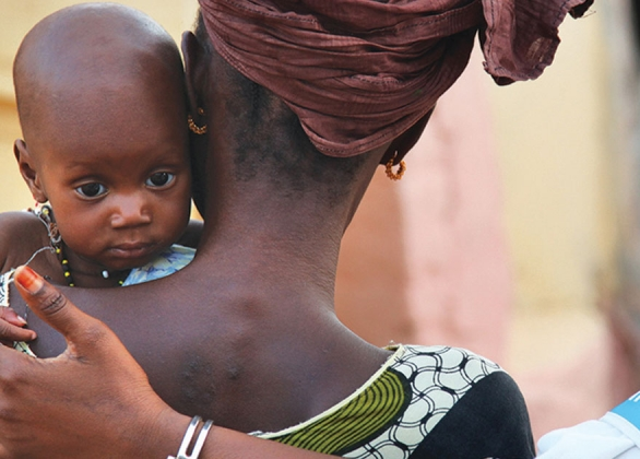 UNICEF aid worker puts her arm around mother and baby