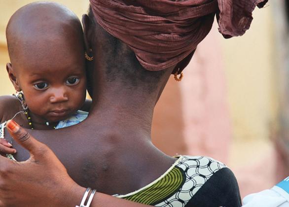 Une travailleuse de l'UNICEF passe son bras autour d'une mère et de son bébé.