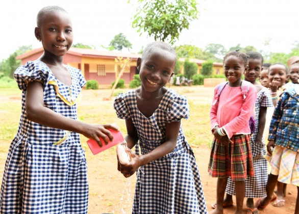 Girls wash their hands at a school.