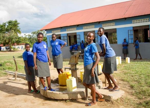 School girls stand beside water pump.