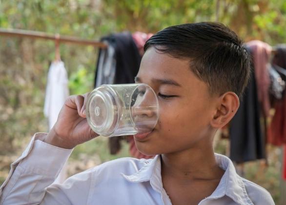 Un enfant tient un comprimé de purification de l'eau dans une main