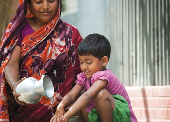 a mother pours clean water on her child's hands