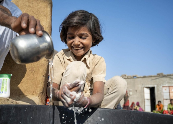 A community member helps her child wash her hands with soap using the correct washing methods in Bangladesh.