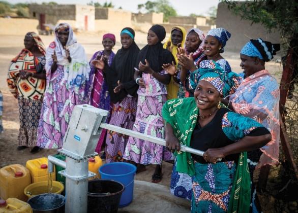 Une fille souriante puise de l'eau à une pompe à eau.