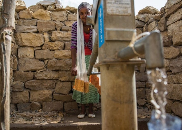 smiling girl pumps water from a water pump