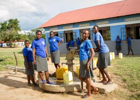 School girls stand beside water pump