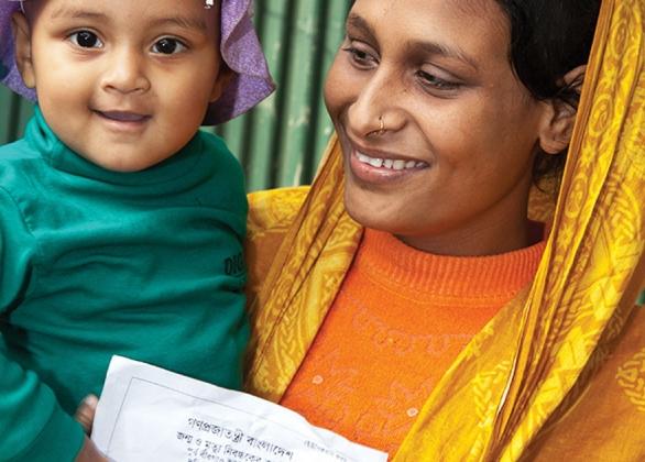 Une mère et son bébé tenant un extrait de naissance.