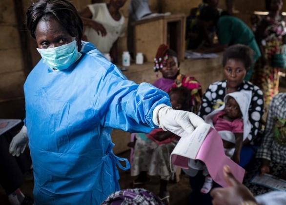 A nurse hands a patient a vaccine card after helping immunize children