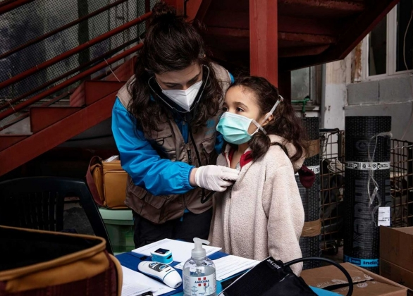 Child receives a medical screening from a health-care worker