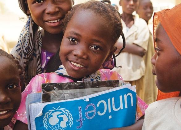 Groupe de filles, dont une tient un cahier de l'UNICEF.