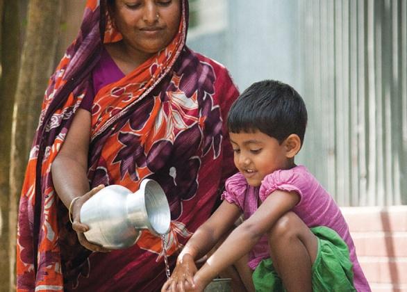 Une mère verse de l'eau potable sur les mains de son enfant.